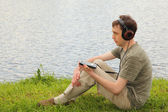 Young man liistens music in headphones sits on grass ashore — Stock Photo