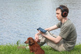 Genç adam liistens müzik kulaklık onun da çim üzerinde oturur — Stok fotoğraf