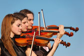 Trio of violinists plays against sky — Stock Photo