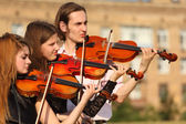 Trio of violinists plays outdoor — Stock Photo