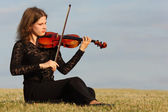 Girl sits on grass and plays violin against sky — Stock Photo
