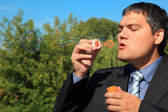 Businessman blows soap bubbles outdoor — Stock Photo