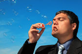Businessman blows soap bubbles against sky — Stock Photo