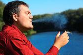Smoking man on river bank — Stockfoto