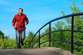 Hombre de camisa roja corre en puente en verano — Foto de Stock