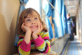 Girl sits in corridor of railway car and looks upward — Stock Photo