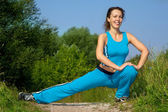 Beautiful slim woman stretching outdoors — Stock Photo