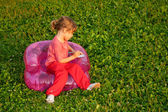 Young writing girl sits in inflatable armchair — Stock Photo