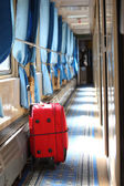 Red suitcase in corridor of railway wagon — Stock Photo