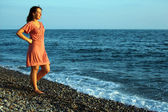 Young woman stands ashore of sea — Stock Photo
