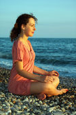 Young woman sits and meditation ashore of sea — Stock Photo