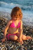 Little girl sits on beach — Foto de Stock