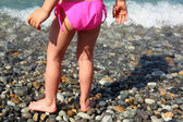 Children's feet on seacoast — Stock Photo