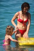 Madre con hija en mar con colchón inflable — Foto de Stock