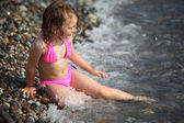 Little girl sits ashore in waves — Stock Photo