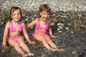 Two little girls sit ashore in water — Stock Photo