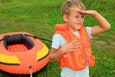 Boy keeps watch and inflatable boat on lawn — Stock Photo