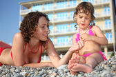 Mother with daughter on pebble in swimwear — Stockfoto
