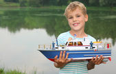 Boy with toy ship in hands ashore — Stock Photo