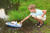 Boy sends toy ship in floating — Stock Photo