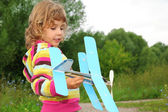 Little girl with toy airplane in hands outdoor — Stock Photo