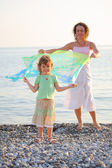 Mother with daughter stand on seacoast with shawl in hands — Stock Photo