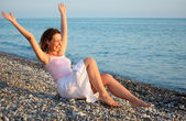 Young woman sits ashore of sea with rised hands — Stock Photo