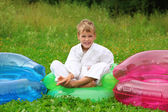 Karate boy sits in inflatable armchair on lawn — Stock Photo
