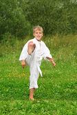 Karate boy kick a leg outdoor — Stock Photo