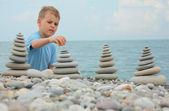 Pebble beach boy ve taş yığınları — Stok fotoğraf