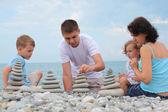 家族の小石のビーチで石のスタックを構築します — ストック写真