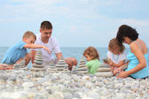 Family builds stone stacks on pebble beach — Stock Photo
