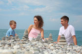 Family and stone stacks on pebble beach — Stock Photo