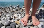 Dos piernas y pilas de piedra en pebble beach — Foto de Stock