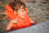 Little girl in inflatable waistcoat in pool — Stock Photo