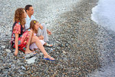 Happy family with little girl sitting on stony beach, Looking af — Стоковое фото