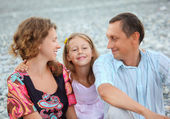 Happy family with little girl sitting on stony beach, parents lo — Stock Photo