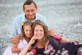 Happy family with little girl sitting on stony beach — Stock Photo