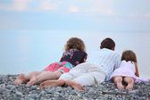 Happy family with little girl lying on stony beach, lying back — Foto Stock