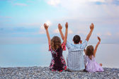 Happy family with little girl sitting on stony beach lifted hand — Stock Photo