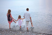 Happy family with little girl go in water, standing back — Stock Photo