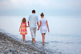 Happy family with little girl walk on beach in evening — Foto de Stock