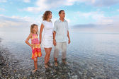 Happy family with little girl standing knee-deep in sea on beach — Stock Photo
