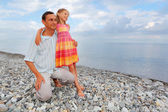 Young man with little girl on stony beach — Stock Photo