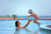 Beautiful woman catches little girl jumping in pool against sea — Stock Photo