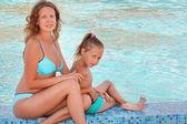 Bella mujer con niña sentarse cerca de piscina — Foto de Stock