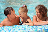 Happy family with little girl bathe in pool — Stock Photo