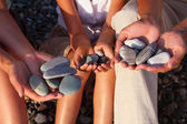 Pebbles in family with girl hands — Stock Photo