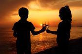 Silhuetas de menino e menina com óculos no pôr do sol do mar — Foto Stock