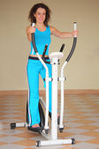 Smiling young woman on training apparatus, full body — Stock Photo